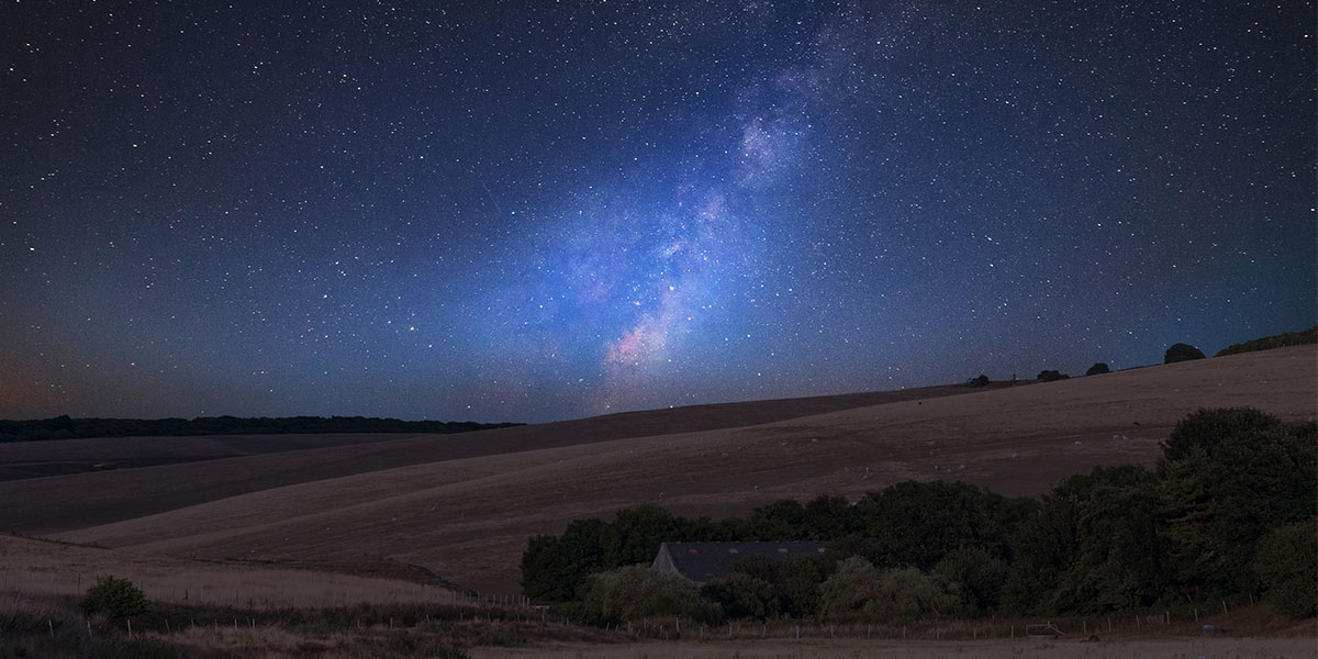 Vibrant Milky Way composite image over landscape of English countryside